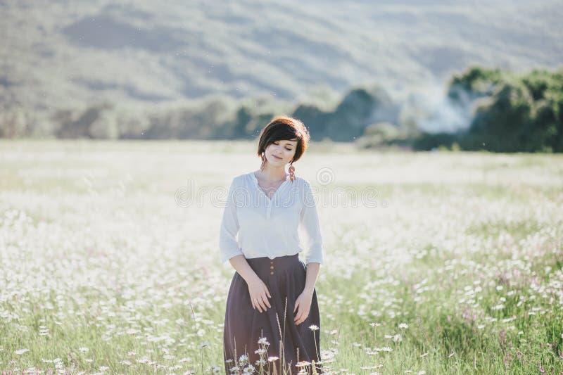 Mulher bonita nova que aprecia o campo da camomila entre montanhas imagens de stock