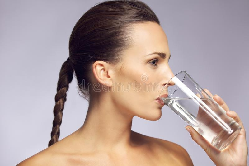 Mulher bonita nova que bebe um vidro da água mineral imagens de stock