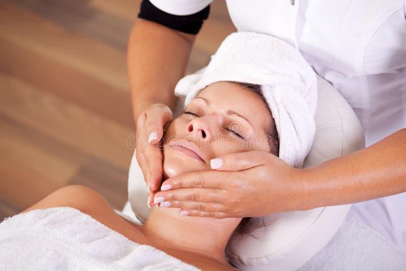 Mulher bonita nova que começ a massagem facial foto de stock