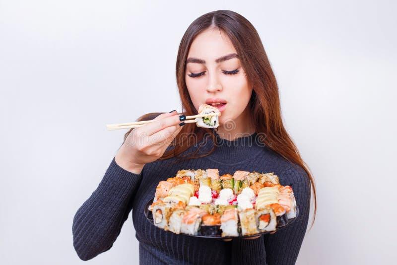 Mulher bonita nova que come o sushi, tiro do estúdio no backgr branco fotografia de stock royalty free