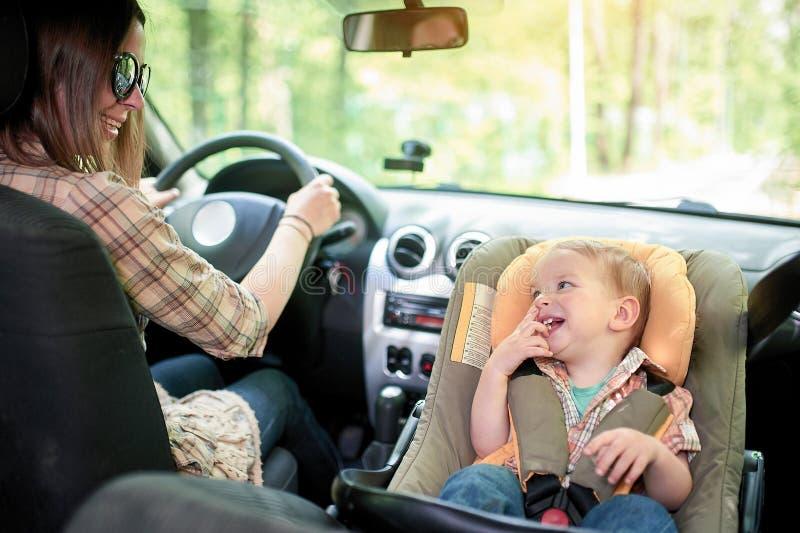 Mulher bonita nova que conduz um carro Em um assento dianteiro montou o assento da seguran?a da crian?a com um menino bonito da c imagens de stock royalty free