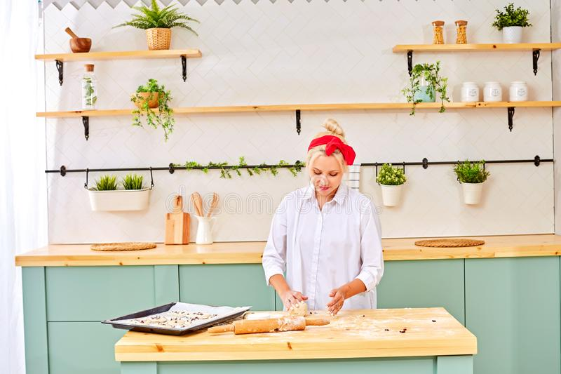 Mulher bonita nova que coze na cozinha brilhante da casa foto de stock