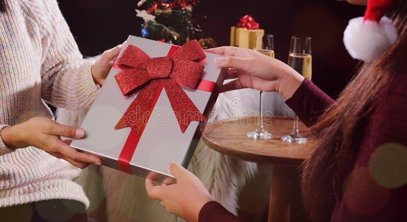 Mulher bonita nova que dá um presente ao amigo Natal ou novo fotografia de stock