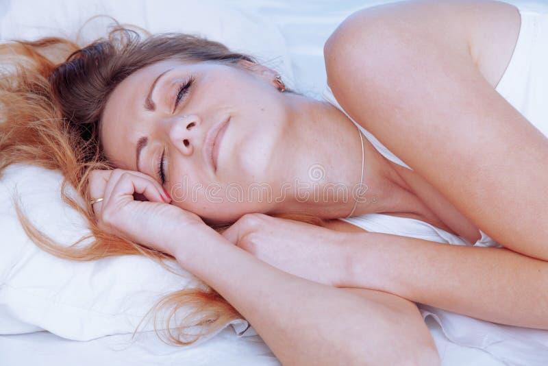 Mulher bonita nova que dorme em sua cama Relaxe o conceito foto de stock