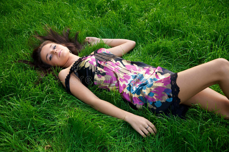 Mulher bonita nova que encontra-se em uma grama verde foto de stock royalty free