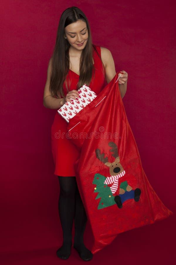 Mulher bonita nova que esconde seu presente do Natal ao saco fotografia de stock