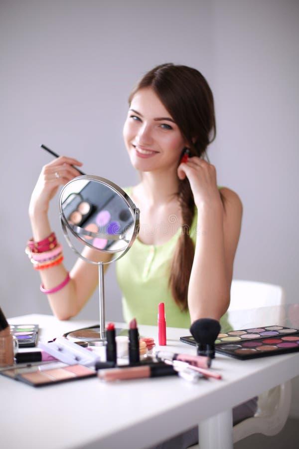 Mulher bonita nova que faz a composição perto do espelho, sentando-se na mesa fotografia de stock