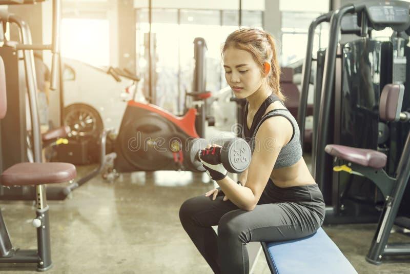 Mulher bonita nova que faz exercícios com peso no gym imagem de stock