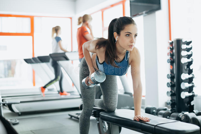 Mulher bonita nova que faz exercícios com peso no gym imagem de stock royalty free