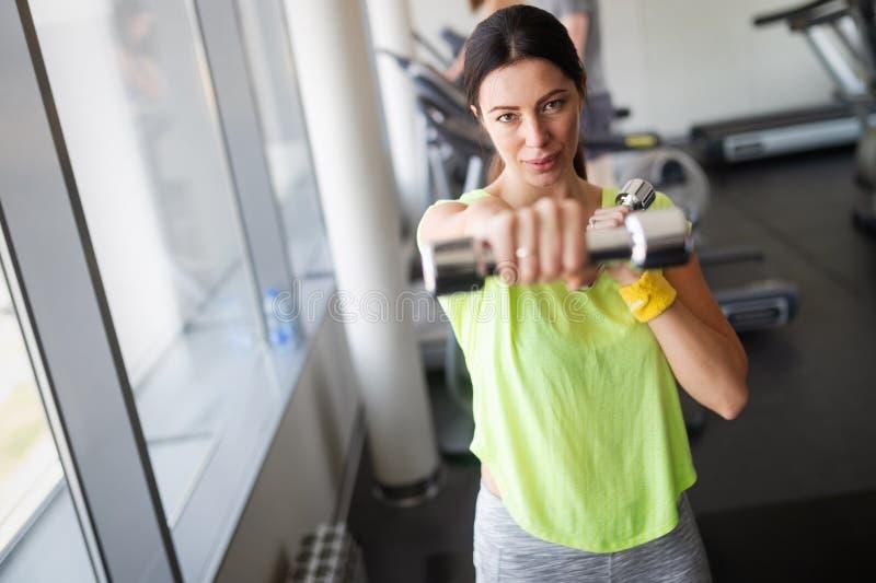 Mulher bonita nova que faz exerc?cios com peso no gym foto de stock royalty free
