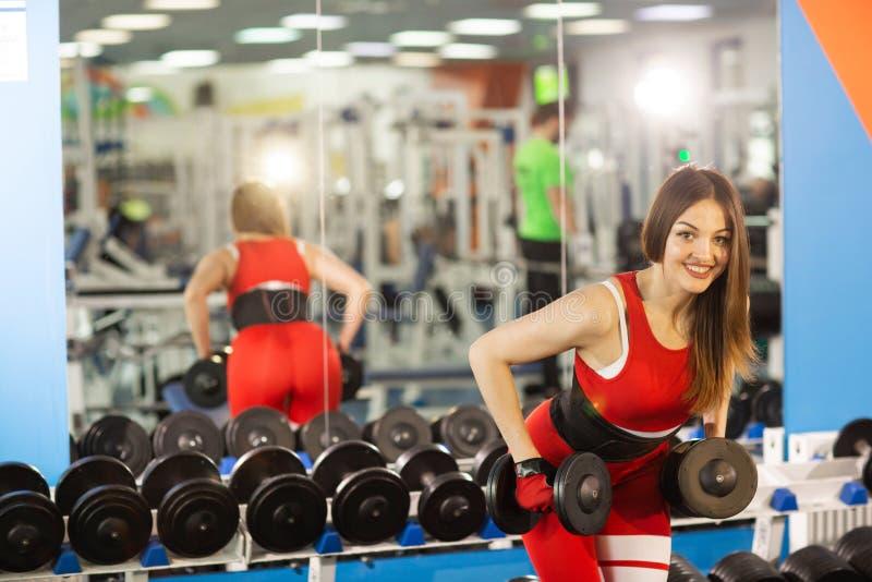 Mulher bonita nova que faz exerc?cios com peso no gym A menina de sorriso contente est? apreciando com seu processo do treinament foto de stock royalty free