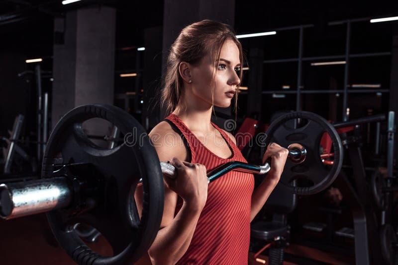 Mulher bonita nova que faz o exercício com barra em um gym Menina atlética que faz o exercício em um fitness center fotos de stock royalty free