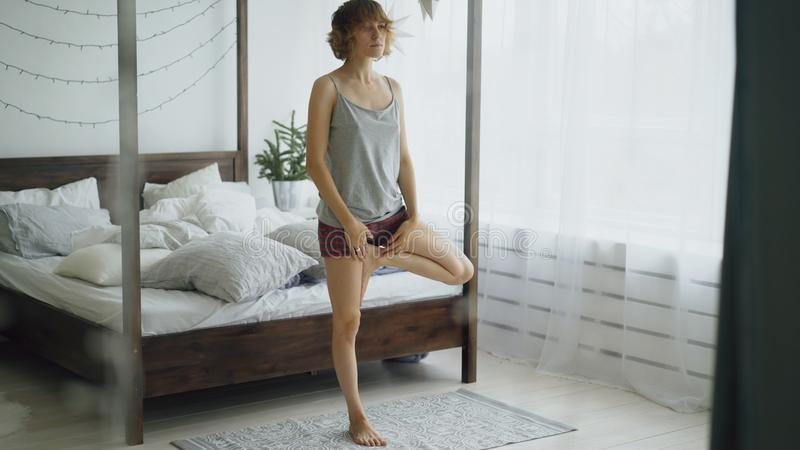 Mulher bonita nova que faz o exercício da ioga perto da cama no quarto em casa foto de stock