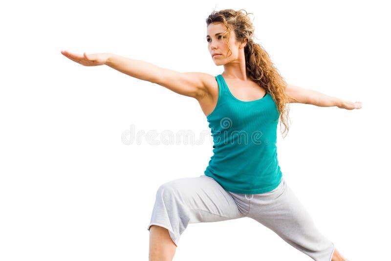 Mulher bonita nova que faz a pose do guerreiro da ioga imagem de stock