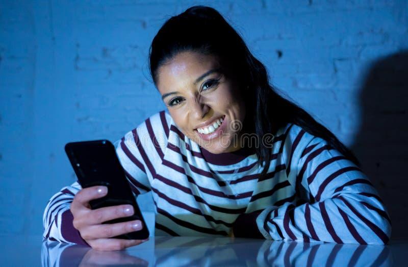 Mulher bonita nova que flerta e que conversa em seu telefone esperto tarde na noite imagem de stock