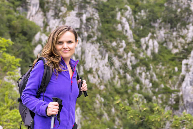 Mulher bonita nova que guarda a caminhada do polo ao escalar o ro imagens de stock