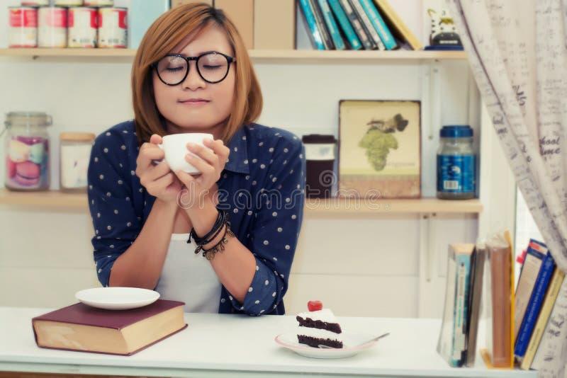A mulher bonita nova que guarda o copo de café era cheiro perfumado em c fotografia de stock