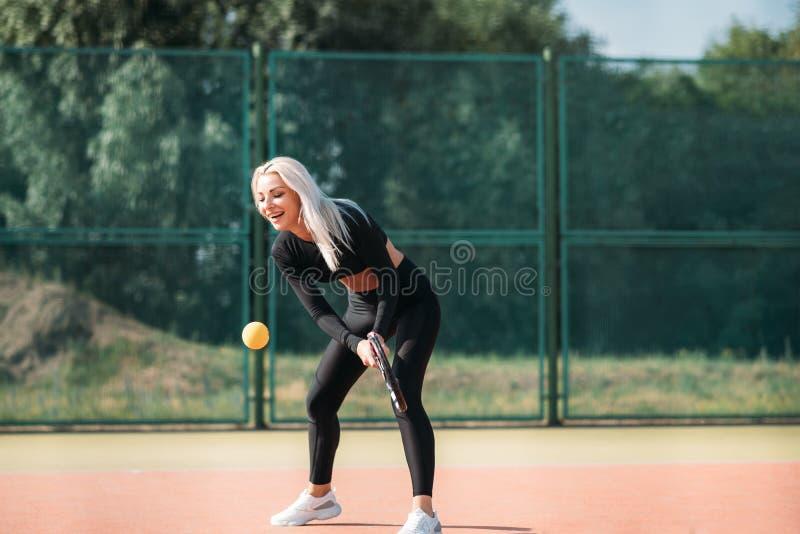 Mulher bonita nova que joga o tênis em uma corte estilo de vida saud?vel do esporte imagens de stock