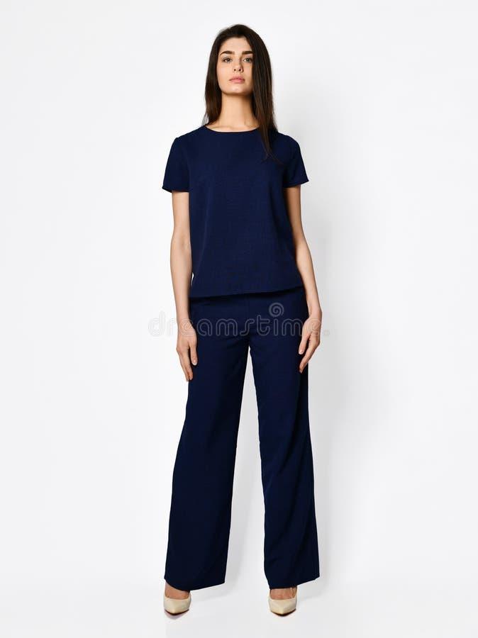 Mulher bonita nova que levanta em escuro novo - blusa azul com o traje ocasional do verão da forma das calças fotografia de stock royalty free