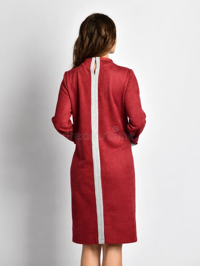 Mulher bonita nova que levanta em escuro novo - opinião traseira vermelha de revestimento de vestido do inverno da forma foto de stock royalty free