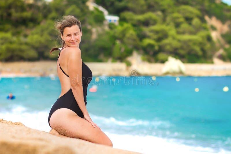 Mulher bonita nova que levanta na praia arenosa do mar A menina atrativa senta-se na areia da praia imagens de stock