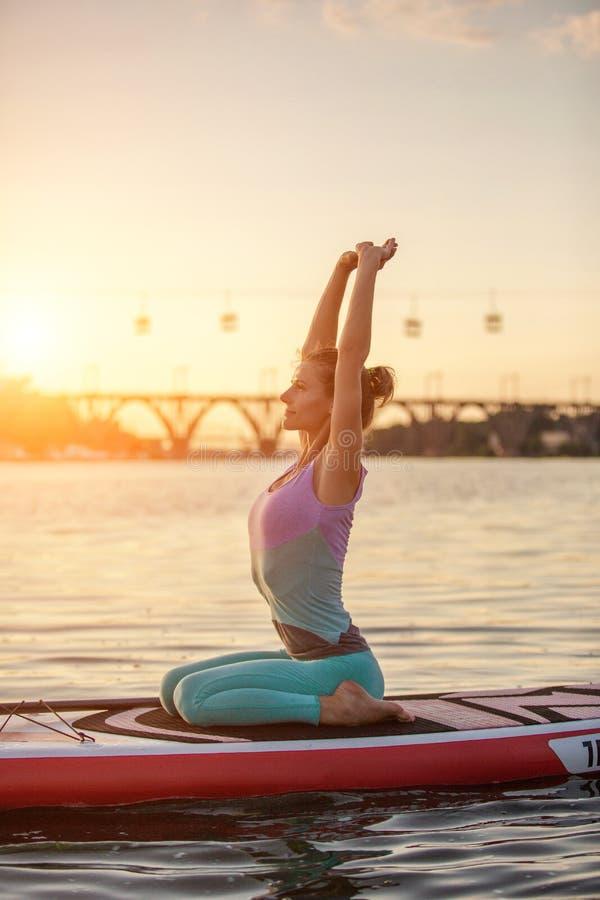Mulher bonita nova que medita em um mar no SUP que paddleboarding Estilo de vida saudável imagem de stock