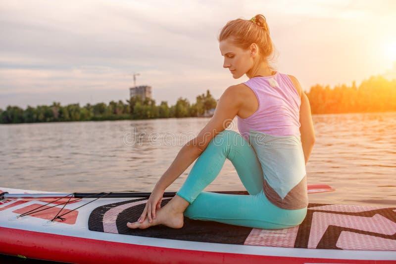Mulher bonita nova que medita em um mar no SUP que paddleboarding Estilo de vida saudável imagem de stock royalty free