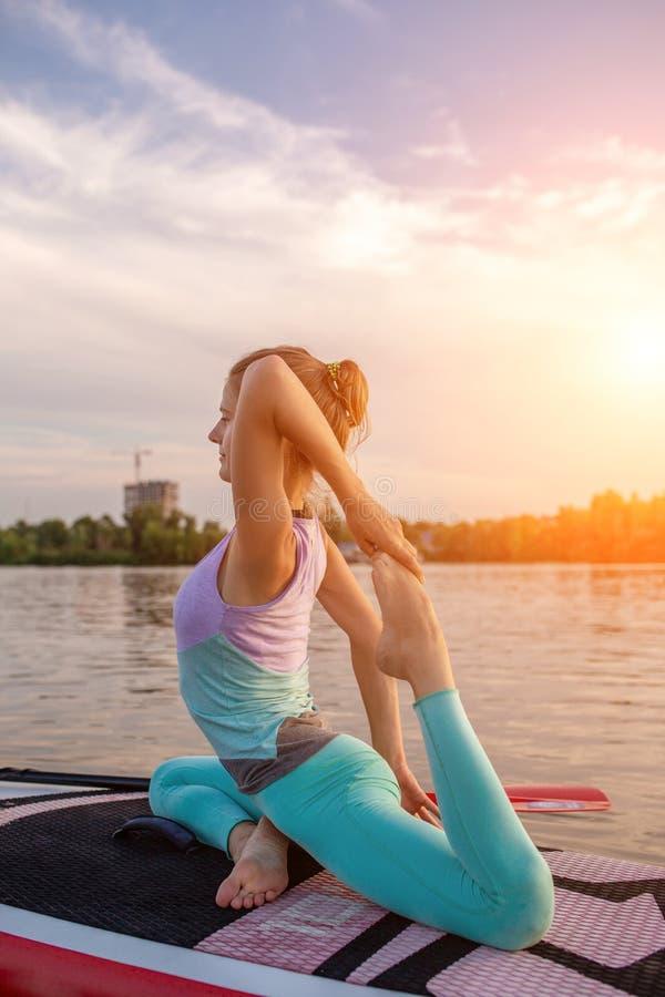 Mulher bonita nova que medita em um mar no SUP que paddleboarding Estilo de vida saudável fotografia de stock