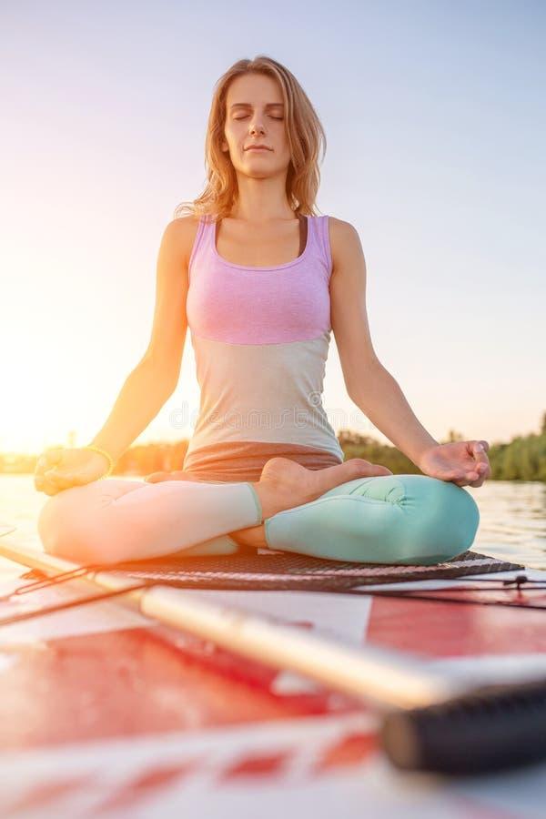 Mulher bonita nova que medita em um mar no SUP que paddleboarding Estilo de vida saudável fotos de stock