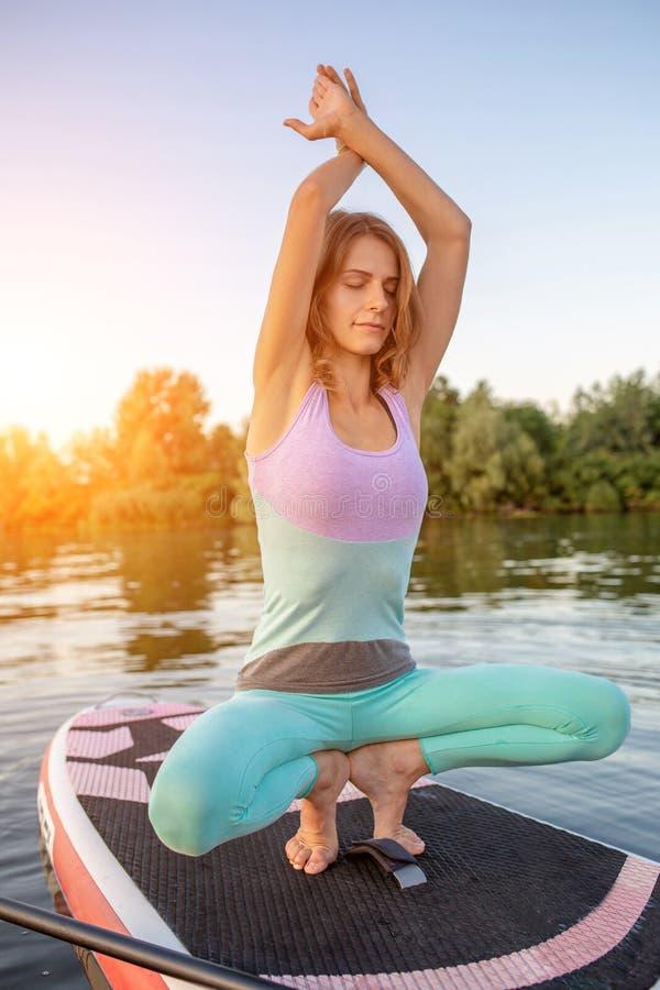 Mulher bonita nova que medita em um mar no SUP que paddleboarding Estilo de vida saudável imagens de stock