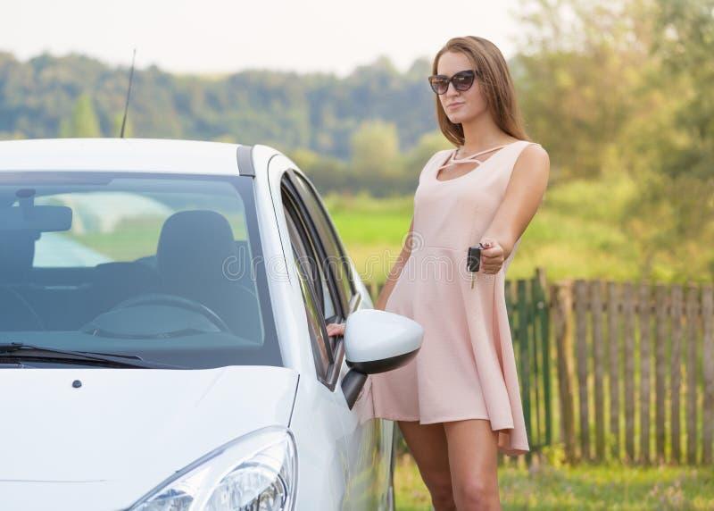 Mulher bonita nova que mostra a chave do carro novo imagem de stock
