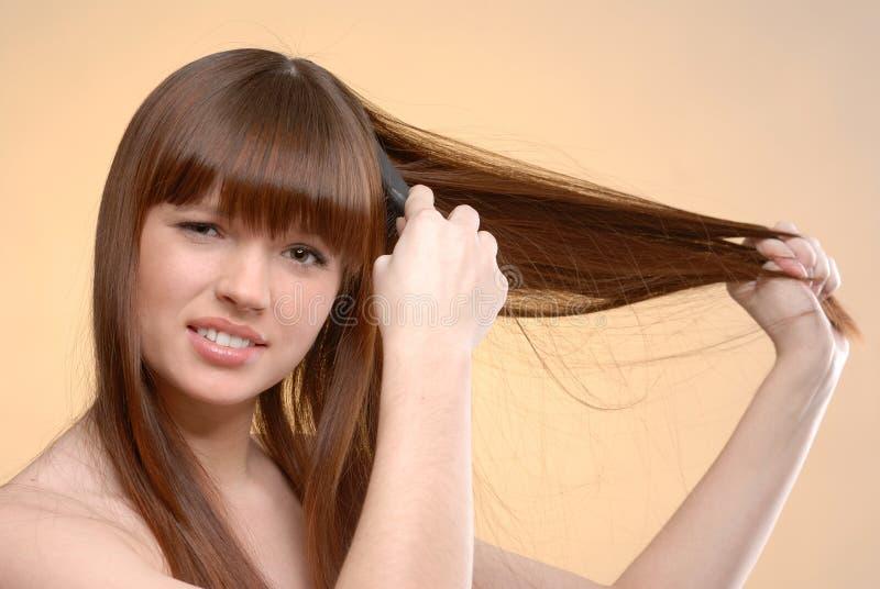 Mulher bonita nova que penteia seu cabelo imagem de stock
