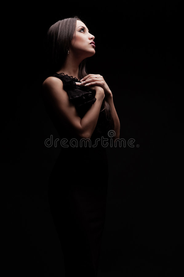 Mulher bonita nova que praying na escuridão imagens de stock