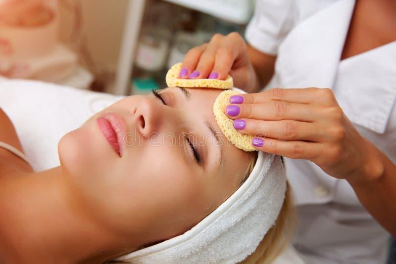 Mulher bonita nova que recebe o tratamento facial da massagem e dos termas fotografia de stock