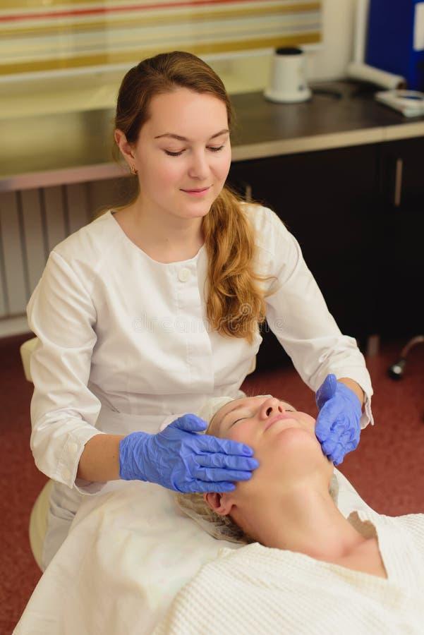 Mulher bonita nova que recebe o tratamento facial da massagem e dos termas no sal?o de beleza imagens de stock royalty free