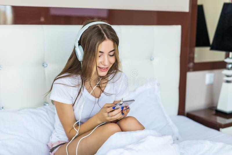 Mulher bonita nova que relaxa em sua cama que escuta a música fotos de stock royalty free