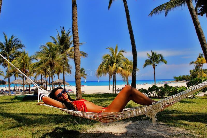 Mulher bonita nova que relaxa na rede na praia tropical fotos de stock royalty free