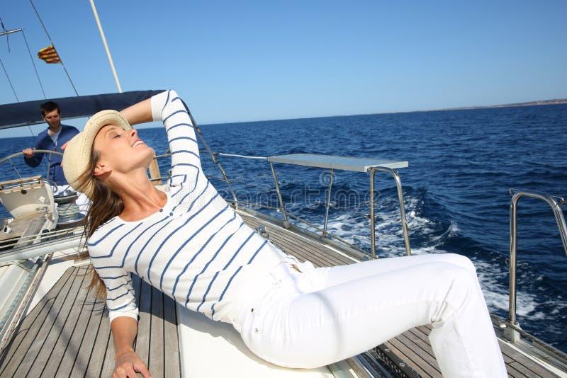Mulher bonita nova que relaxa no barco de navigação imagem de stock royalty free