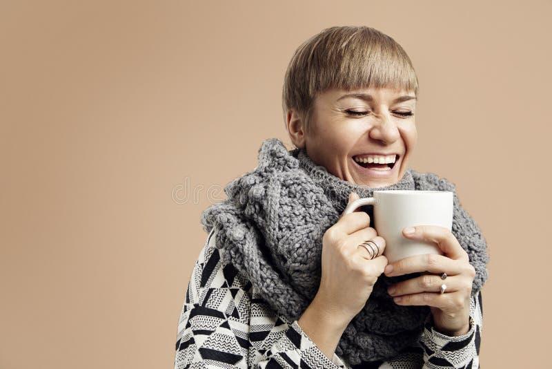 Mulher bonita nova que ri com um copo branco Fundo bege imagens de stock royalty free