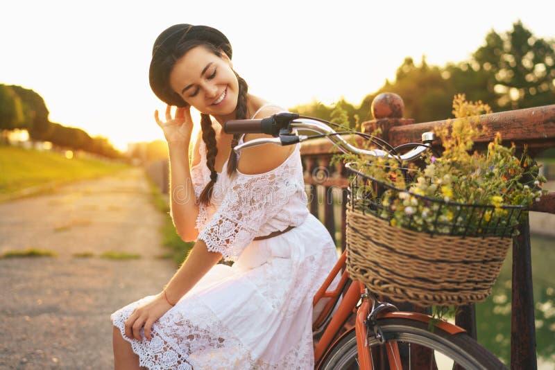 Mulher bonita nova que senta-se em sua bicicleta com as flores no sol fotografia de stock royalty free