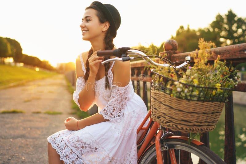 Mulher bonita nova que senta-se em sua bicicleta com as flores no sol fotos de stock royalty free