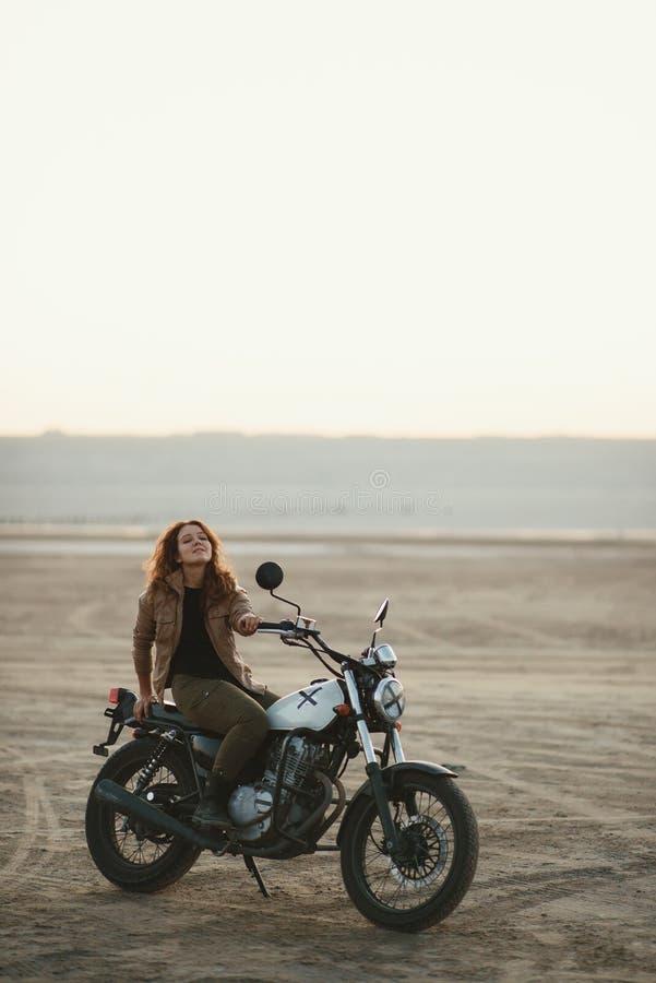 mulher bonita nova que senta-se em sua motocicleta velha do piloto do café no deserto no por do sol ou no nascer do sol foto de stock royalty free