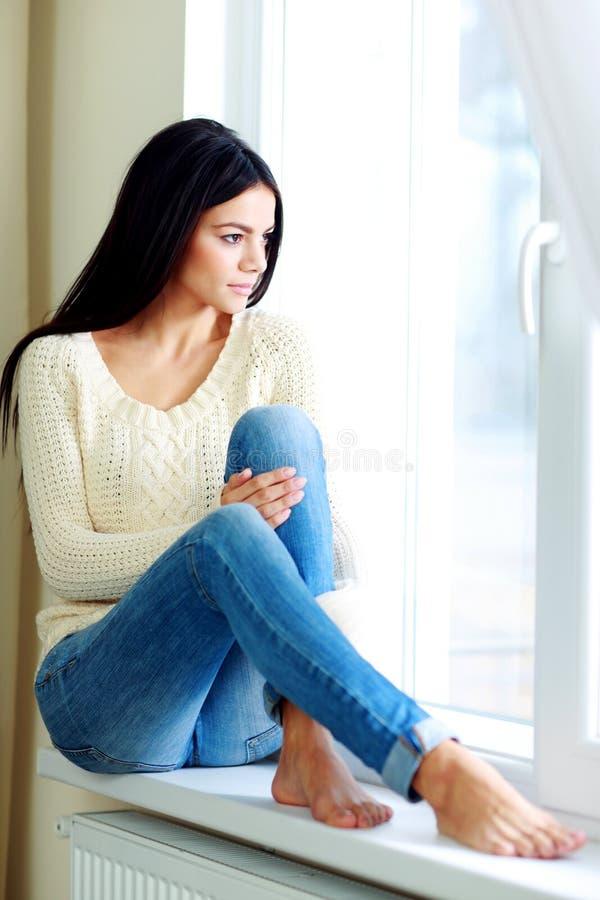 Mulher bonita nova que senta-se em um janela-peitoril fotos de stock royalty free