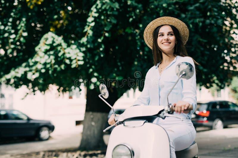 Mulher bonita nova que senta-se em um 'trotinette' fotografia de stock royalty free
