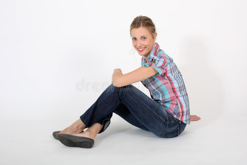 Mulher bonita nova que senta-se isolado para baixo foto de stock