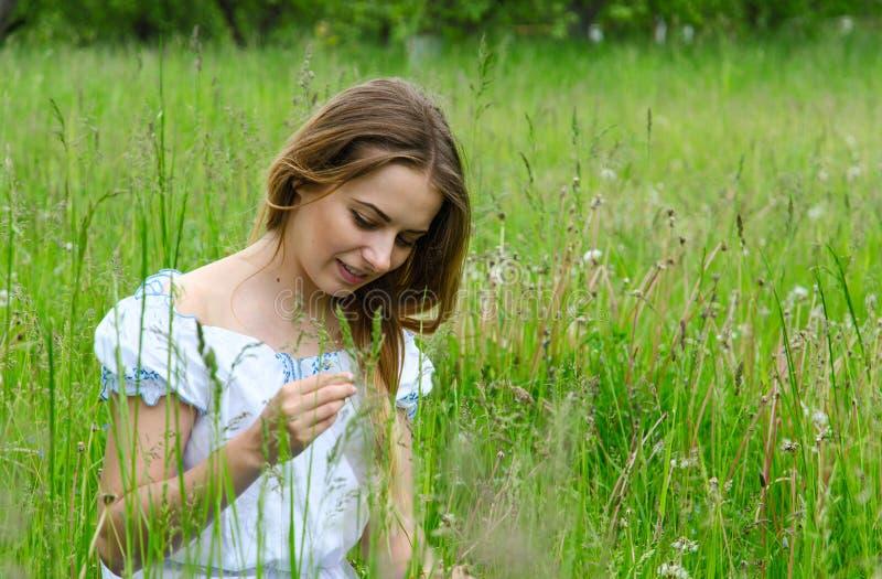 Mulher bonita nova que senta-se na grama de prado imagens de stock