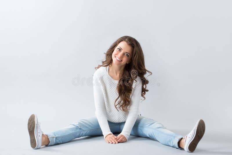 Mulher bonita nova que senta-se no assoalho fotos de stock royalty free