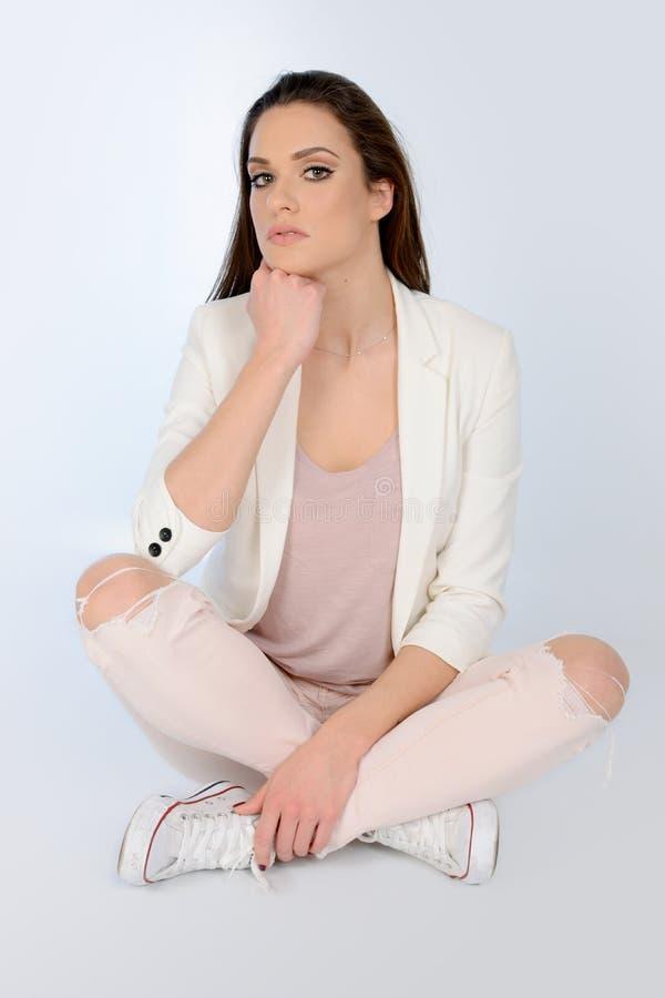 Mulher bonita nova que senta-se no assoalho, no revestimento branco vestindo e nas calças de brim foto de stock