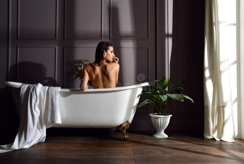 Mulher bonita nova que senta-se no banheiro perto do banho caro da banheira que olha o canto na obscuridade foto de stock