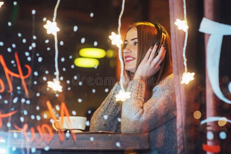 Mulher bonita nova que senta-se no café, café bebendo Escuta modelo a música Natal, ano novo, dia de Valentim, holi do inverno imagem de stock